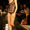 Black bustier and panty with long sheer bustle skirt (front view).