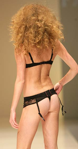 Fauve: Black and prune bra, string and garter belt.